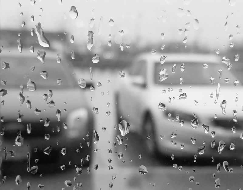 Looking through rainy window at two cars